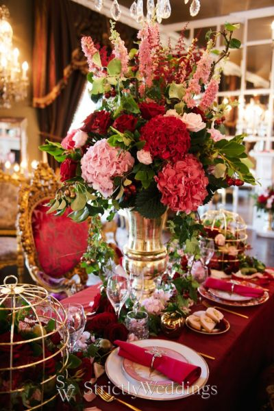 [Image description: A giant bouquet of red and pink flowers sits upon a lavishly decorated dinner table. Image source: Pinterest]
